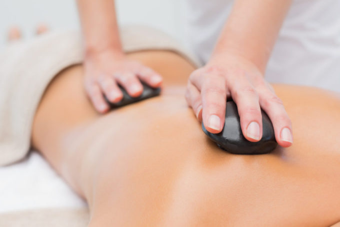 Close up of a beautiful young woman receiving stone massage at spa center