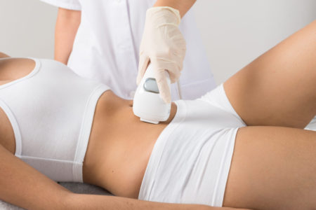 Close-up Of Woman Having Laser Treatment On Belly At Beauty Clinic